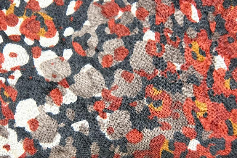 Dunkler Loop-Schal mit rostfarben-beigem Fantasiemuster, Detail Stoff
