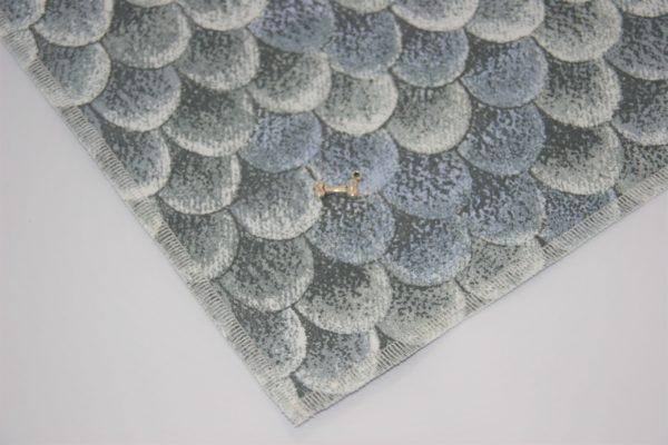 Das Hundehalstuch Reptil ist mit einem modischen Schmuckanhänger verziert